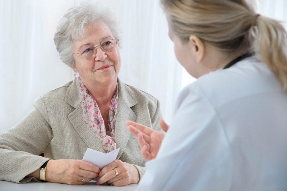 Iäkäs nainen lääkärin vastaanotolla. Nainen on tuonut mukanaan muistiinpanot lääkärikäyntiä varten.