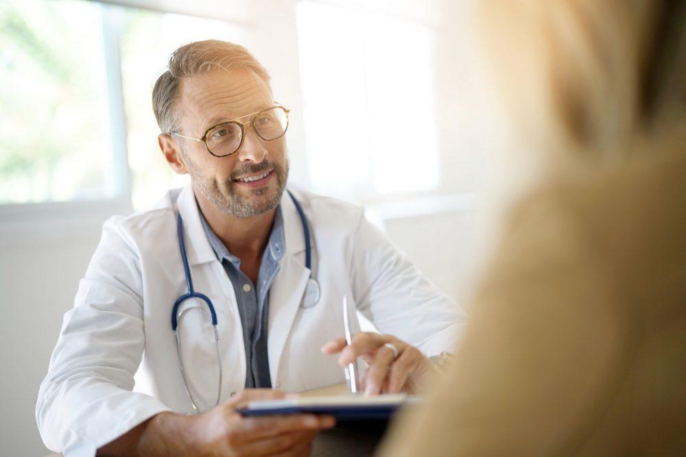 Keski-ikäinen mies lääkäri neuvoo potilasta.