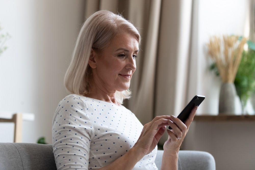 Iäkäs nainen istuu olohuoneen sohvalla ja selaa älypuhelintaan.