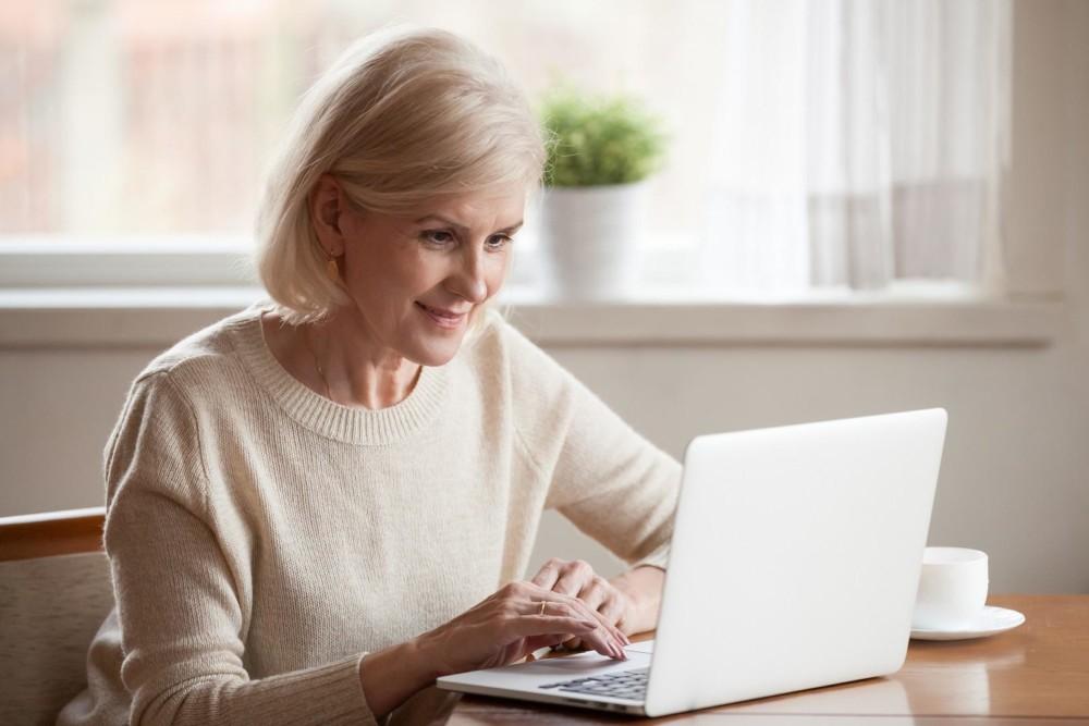 Iäkäs nainen istuu olohuoneen pöydän ääressä ja selaa verkkoa kannettavalla tietokoneellaan.