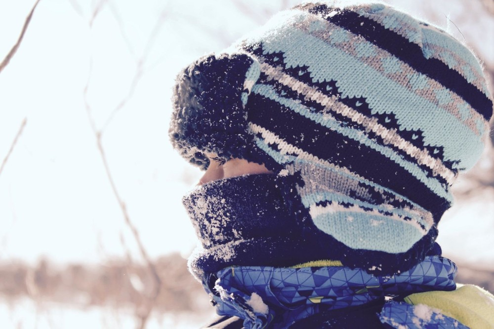 Paksuihin talvivaatteisiin pukeutunut nainen.