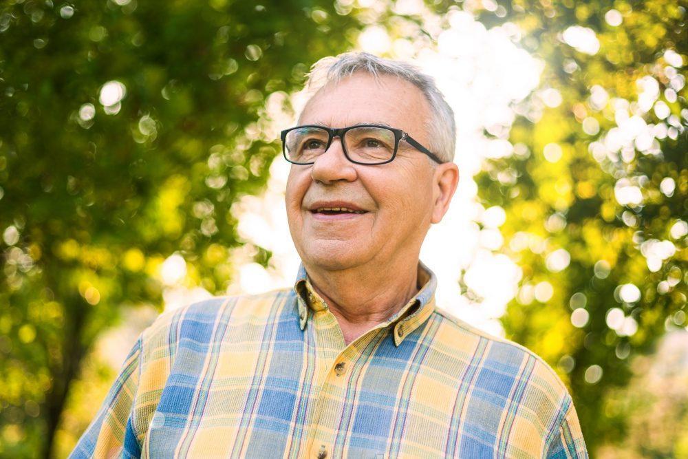 Lähikuva iäkkäästä miehestä puistossa aurinkoisena kesäpäivänä.