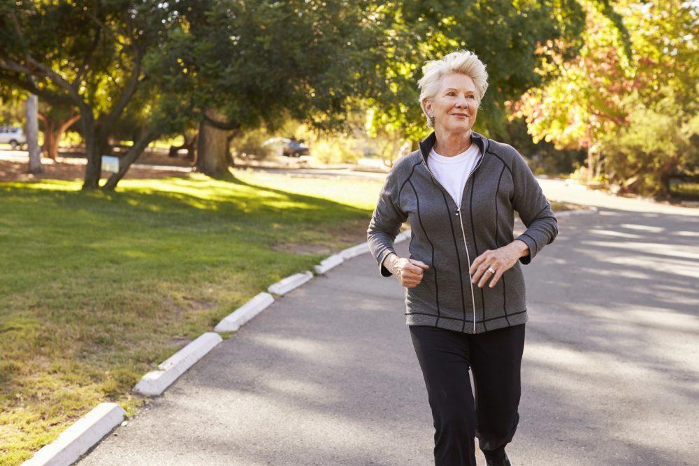 Iäkäs nainen juoksemassa puistossa kauniina kevät päivänä.