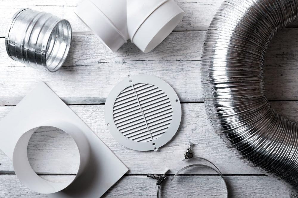 Joukko ilmanvaihdon suodattimia ja muita varusteita valkoisella puupöydällä.