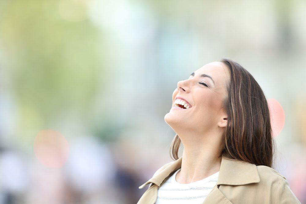 Iloinen nainen vetää syvään henkeä aurinkoisessa kevät maisemassa.