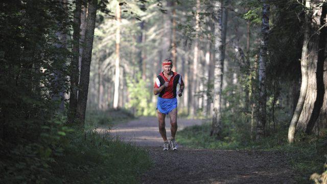 Yksinäinen lenkkeilijä juoksemassa metsäpolulla.