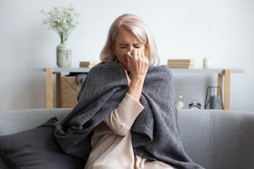 Keski-ikäinen nainen istuu olohuoneen sohvalla. Nainen niistää nenäliinaan ja vaikuttaa muutenkin kipeältä. Hän on kietoutunut vilttiin.