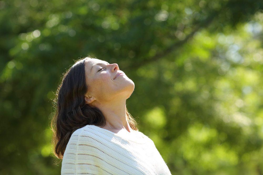 Lähikuva keski-ikäisestä naisesta puistossa aurinkoisena kesäpäivänä.