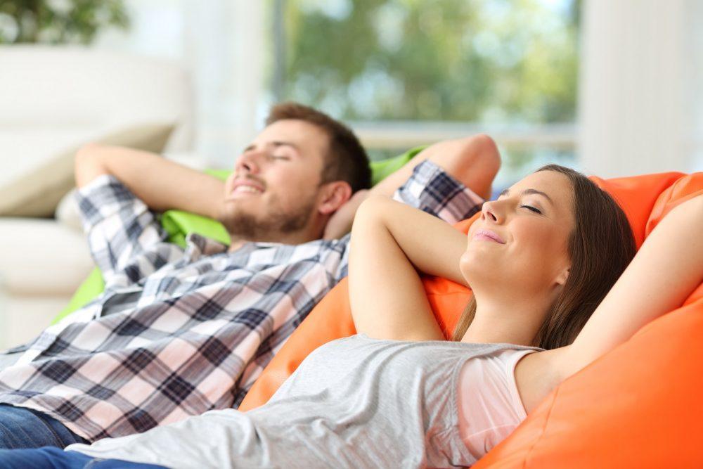 Nuori mies ja nainen makaavat sohvalla ja nauttivat raikkaasta sisäilmasta.