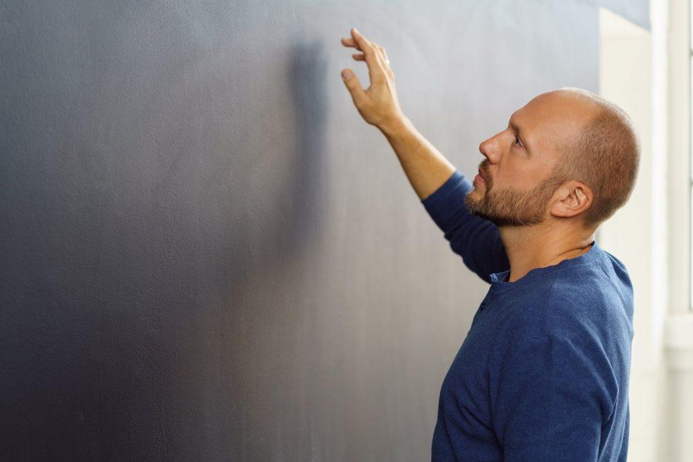 Mies tarkistaa seinän kuntoa.