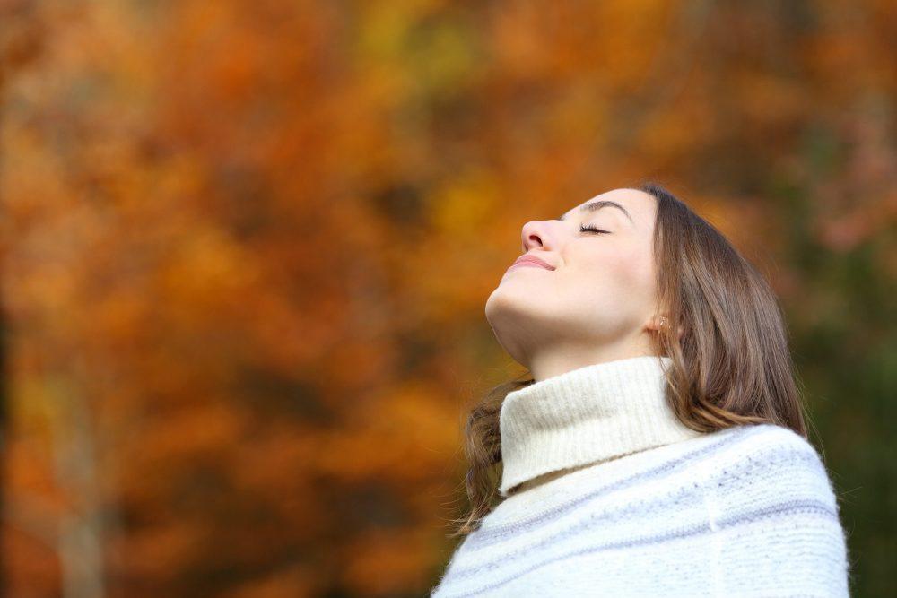 Nainen hengittää syvään syksyisessä metsässä.