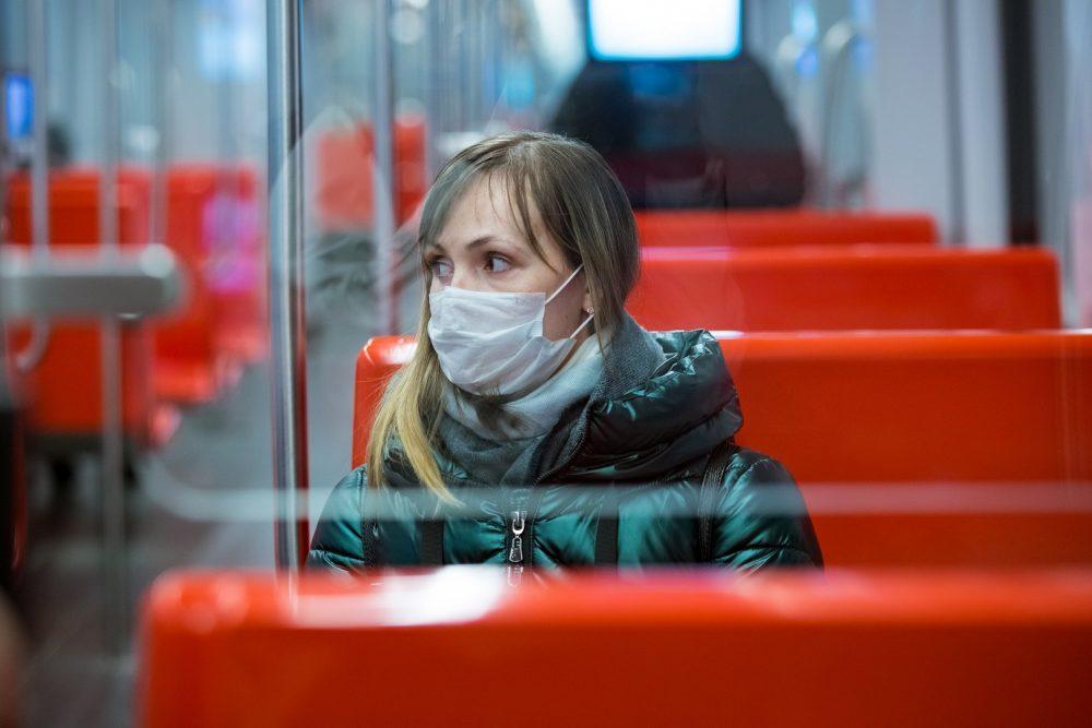 Nainen pitää etäisyyttä metron muihin matkustajiin. Naisella on kasvoillaan kasvomaski.