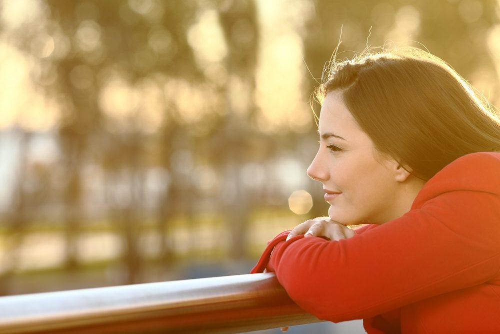 Mietteliäs nainen katsoo maisemia asuntonsa parvekkeelta. Ulkona on aurinkoinen syyspäivä.