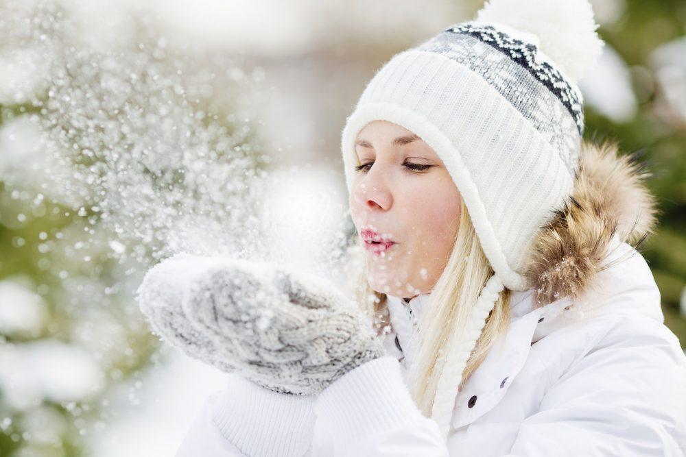 Nainen nauttii talvipäivästä. Nainen puhaltaa hänen lapasissaan olevan lumikasan pois.