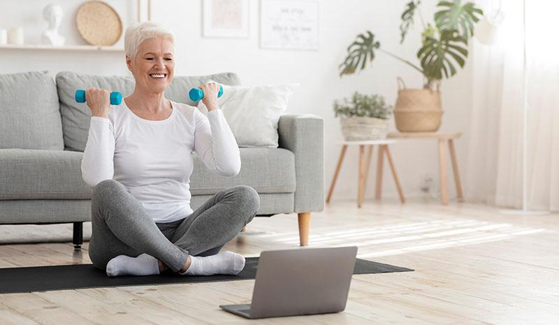 nainen jumppaa kannettavan tietokoneen ääressä