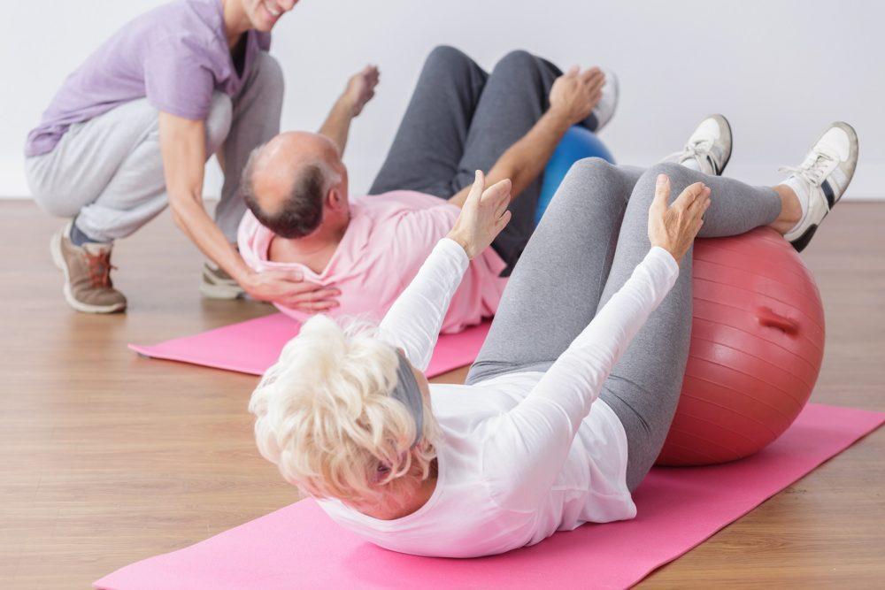 Ohjattua jumppaa iäkkäille ihmisille. Iäkäs mies ja nainen jumppaavat jumppapallon avulla ja ohjaajan avustuksella.