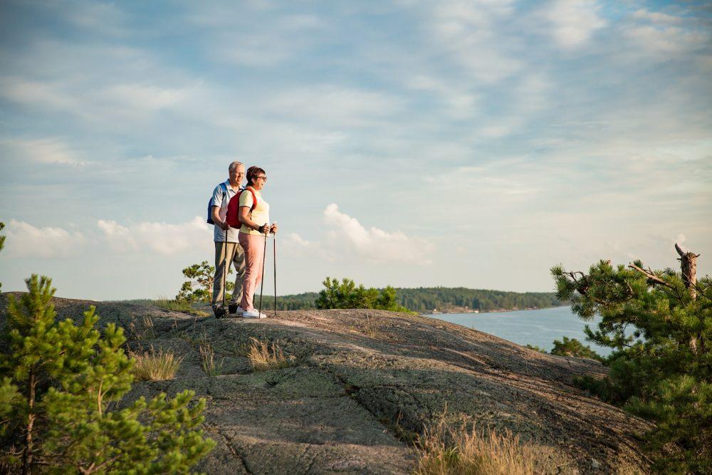 Mies ja nainen sauvakävelyllä. Pari on kiivennyt korkean kallion päälle, josta he ihailevat kaunista järvimaisemaa.
