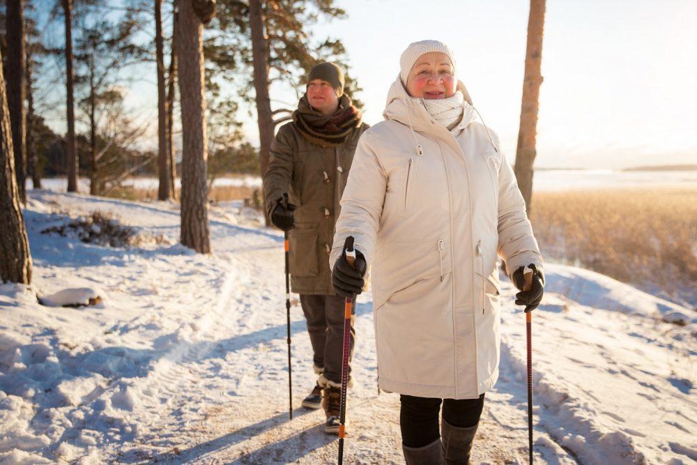 Kaksi henkilöä sauvakävelylenkillä. Kuvan henkilöt kävelevät pitkin lumista metsäpolkua keskellä talvea.