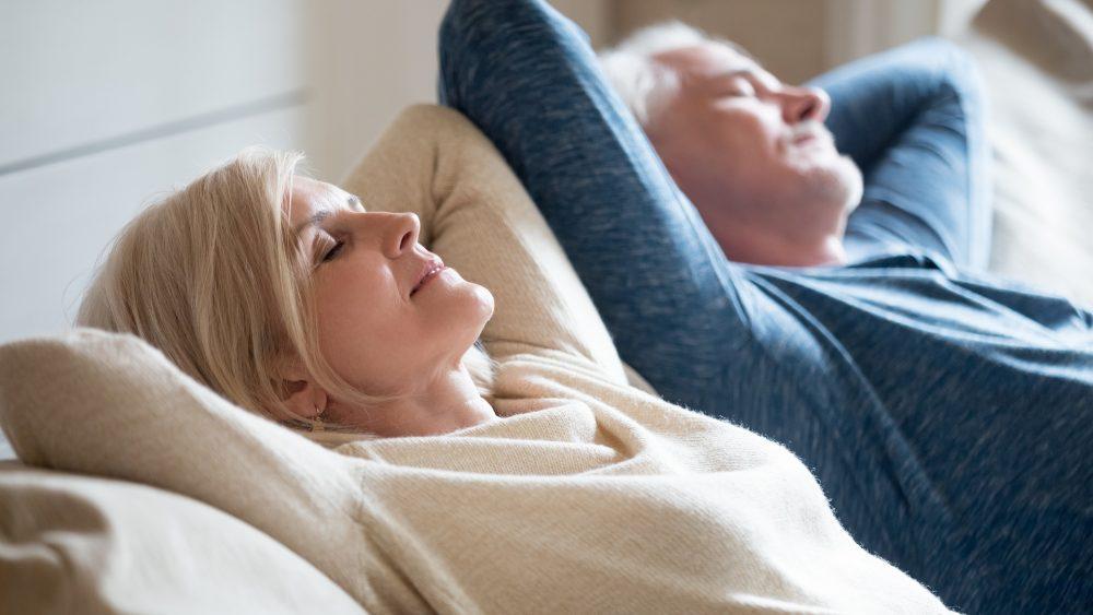 Iäkäs nainen ja mies nauttimassa raikkaasta sisäilmasta olohuoneen sohvalla.