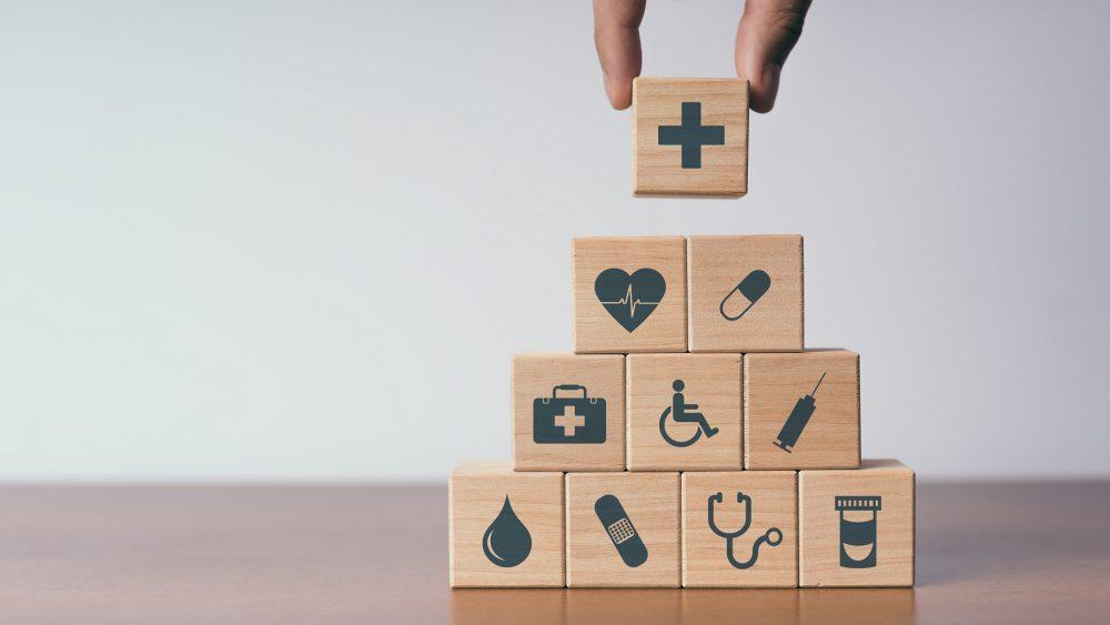Henkilö järjestelee puupalikoita, joissa on terveydenhuoltojärjestelmän eri osa-alueita kuvastavat kuvakkeet. Kuvakkeet kuvastavat muun muassa verta, laastaria, rokotetta ja lääkkeitä.