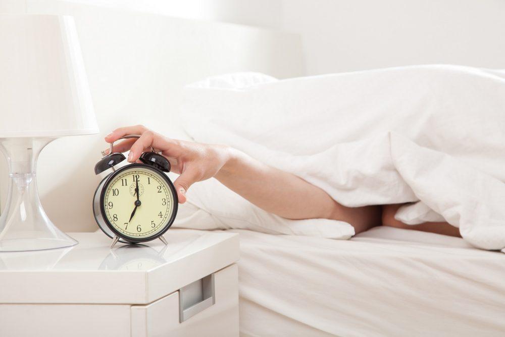 Henkilö sulkemassa herätyskelloa aamu seitsemältä.