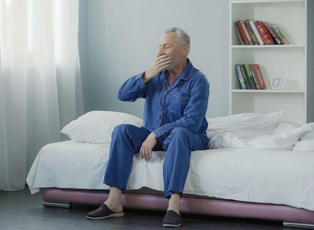 Mies haukottelee sängyllä